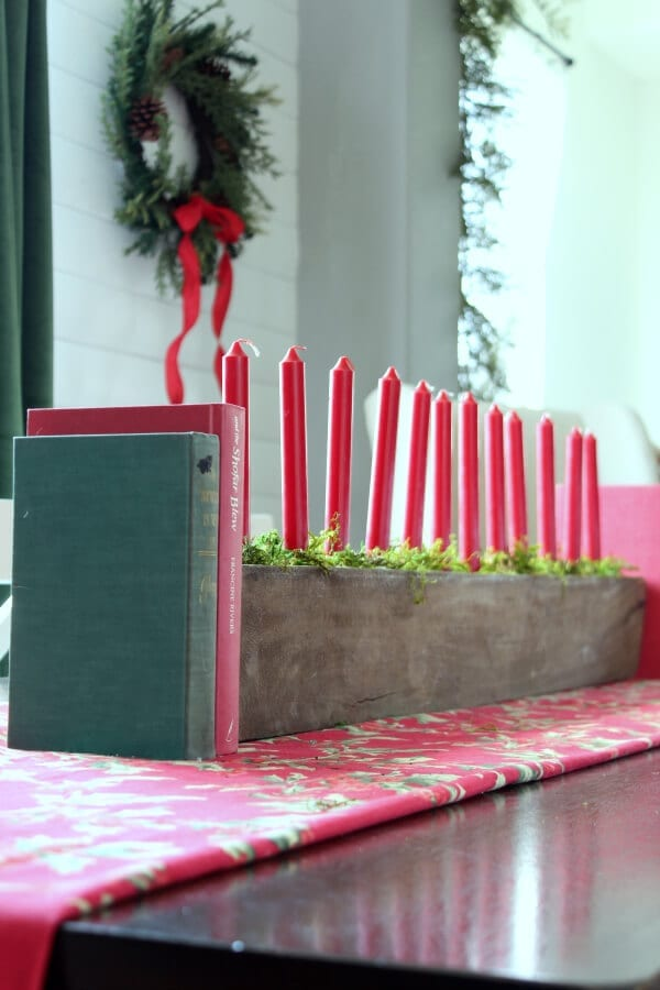 A Christmas centerpiece with moss and candles gives life to our dining room table.