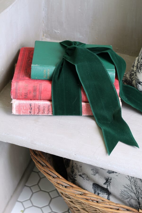 Vintage books wrapped in green velvet ribbon grace our pew for Christmas.