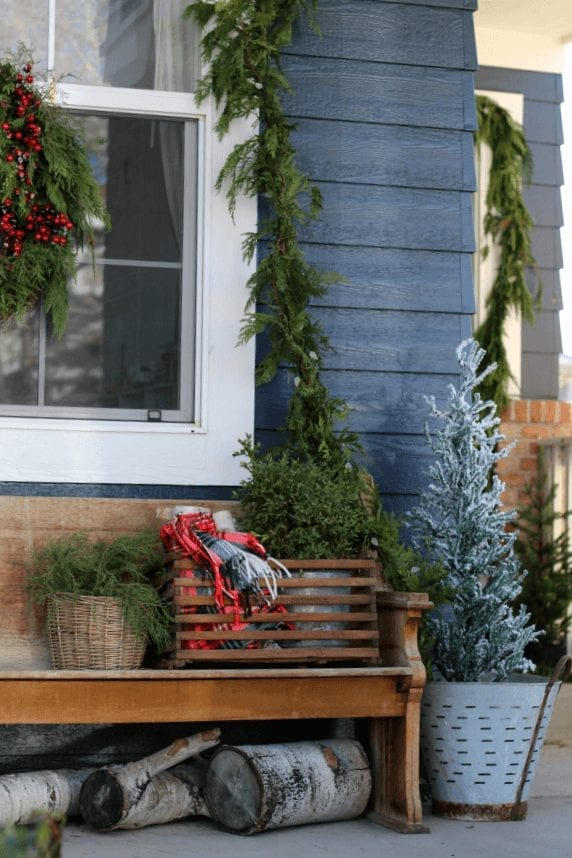 Fresh garland and pops or red and green make this porch ready for Christmas!