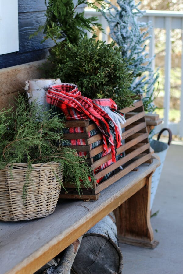 Vintage touches like plaid throws an old bins can make your Christmas porch feel cozy and collected!