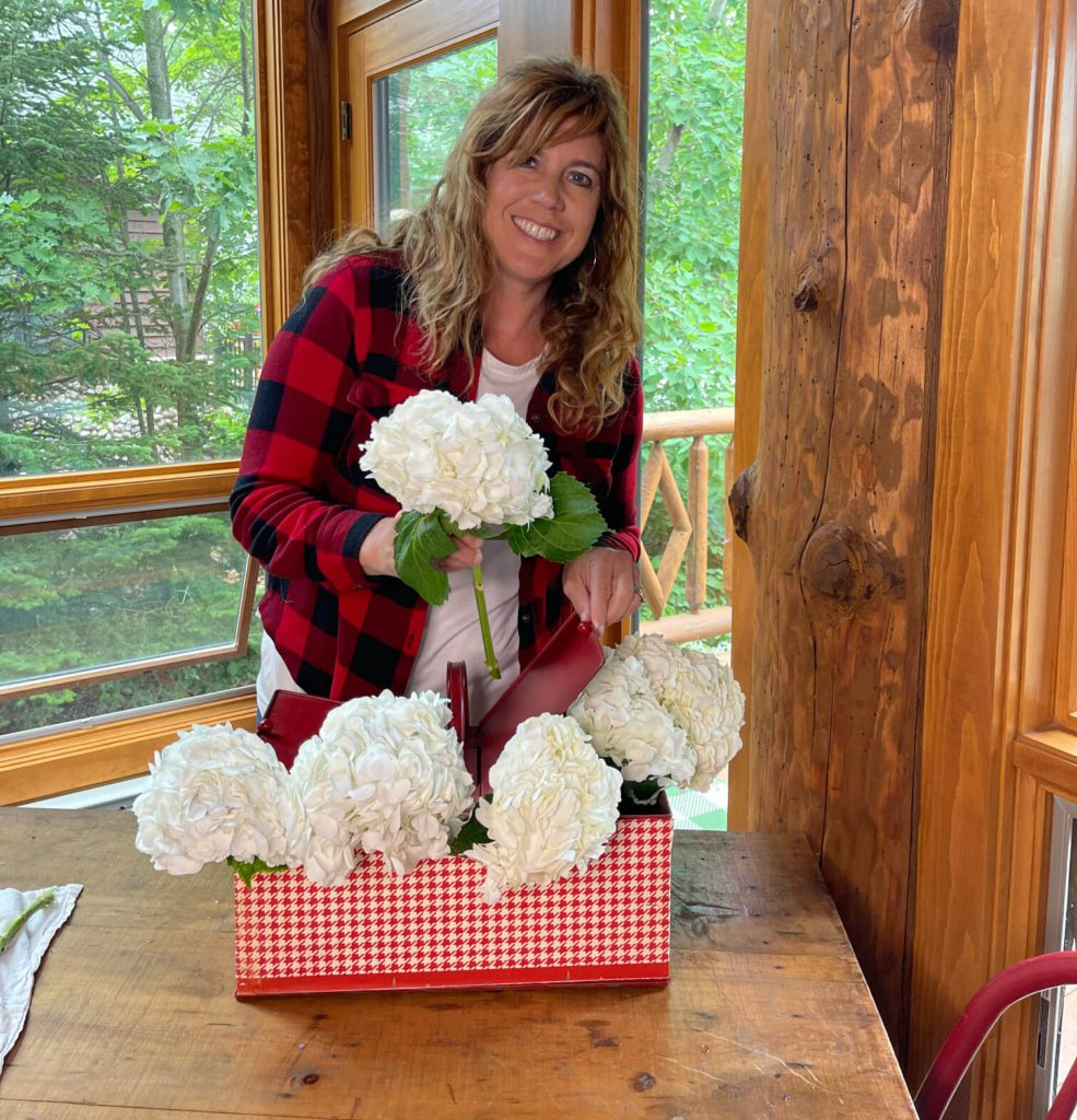Welcome Home Saturday: Summer Tablespace and Centerpiece Decor | Welcome Home Saturday by popular Alabama lifestyle blog, She Gave It A Go: image of a woman arranging some white hydrangeas in a red and white metal basket.