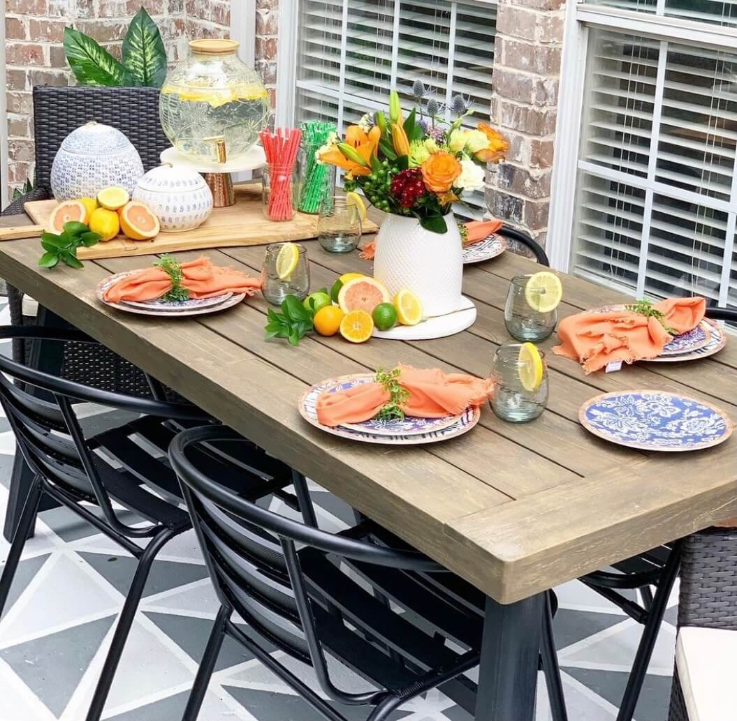 Welcome Home Saturday: Summer Outdoor Table | Welcome Home Saturday by popular Alabama lifestyle blog, She Gave It A Go: image of an outdoor wooden table with black metal chairs decorated with blue and white plates, oranges cloth napkins, clear stemless glasses with lemon wedges, and a white serving board containing clear glass jars filled with straws, a clear glass beverage dispenser and sliced citrus fruit.