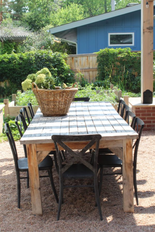 black metal x back chairs flanking a wooden table in our backyard dining space.