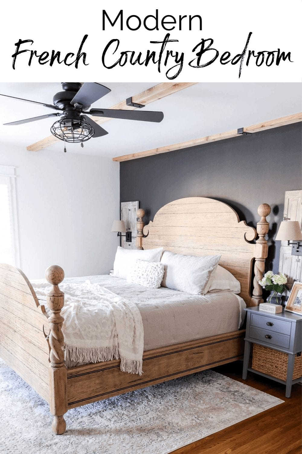 Welcome Home Saturday: Modern French Country Bedroom Refresh | Welcome Home Saturday by popular Alabama lifestyle blog, She Gave It A Go: image of a bedroom with a bed in a wooden farmhouse bed frame with white bedding on a tan and white area rug next to a grey night stand with a wicker basket and vase filled with faux white hydrangeas and a grey accent wall and farmhouse light and fan fixture.
