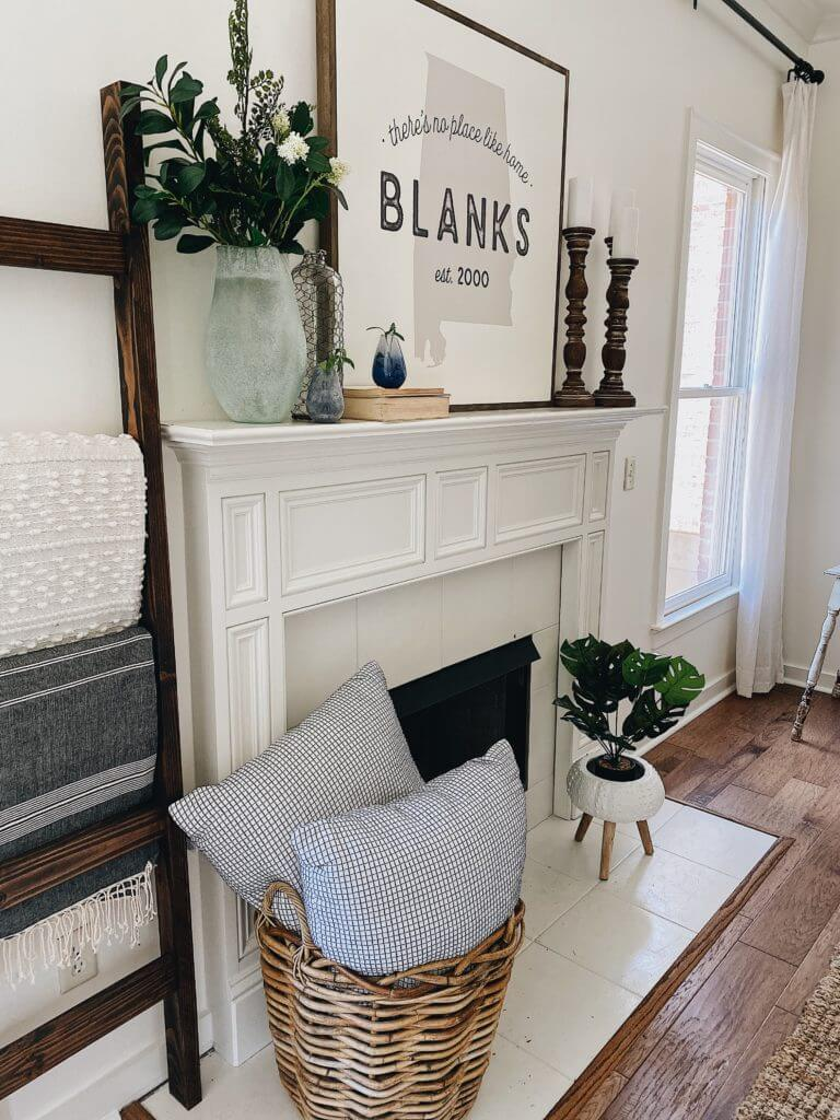 Welcome Home Saturday: Farmhouse fireplace decor items for summer! | Welcome Home Saturday by popular Alabama lifestyle blog, She Gave It A Go: image of a white fireplace decorated with a wooden blanket ladder, woven basket filled with gingham throw pillow, grey plaster vase filled with faux greenery, Alabama state print in a wooden frame, stacked books, and wooden pillar candle stick holders with white pillar candles.