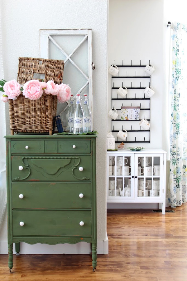 Green boxwood dresser with faux peonies and french lemonade bottles.