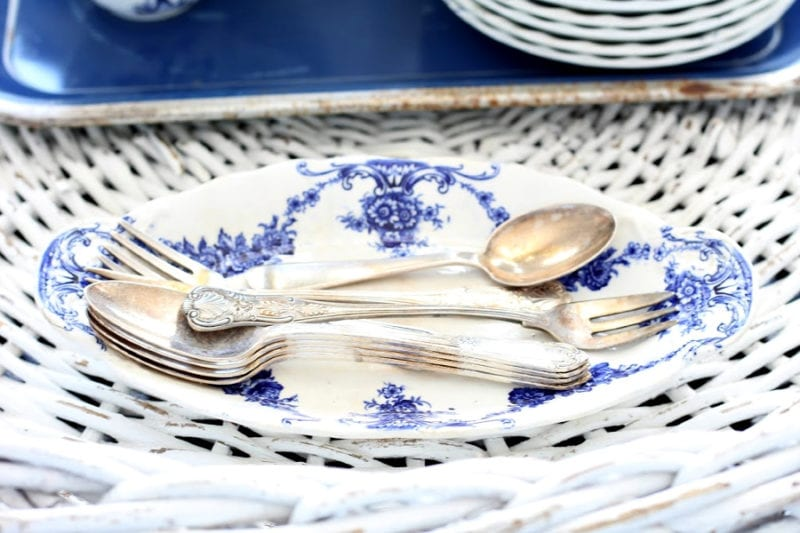 vintage spoons and blue and white ironstone dish for an easy Spring touch on a white wicker tray.