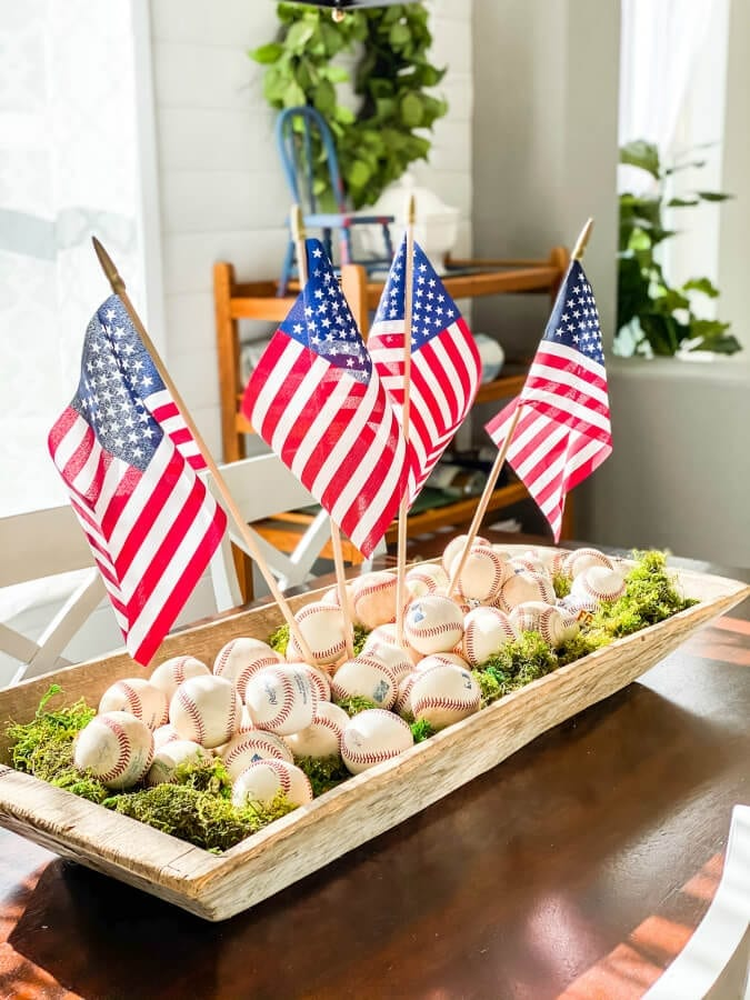 A fun and easy baseball centerpiece! | Welcome Home Saturday by popular Alabama lifestyle blog, She Gave It A Go: image of a baseball centerpiece with baseballs, American flags, and moss.