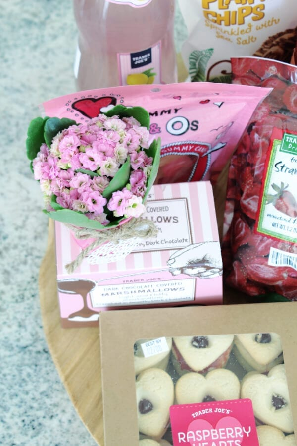 Mini pink flowers in metal containers make this Valentine's Dessert board extra special!