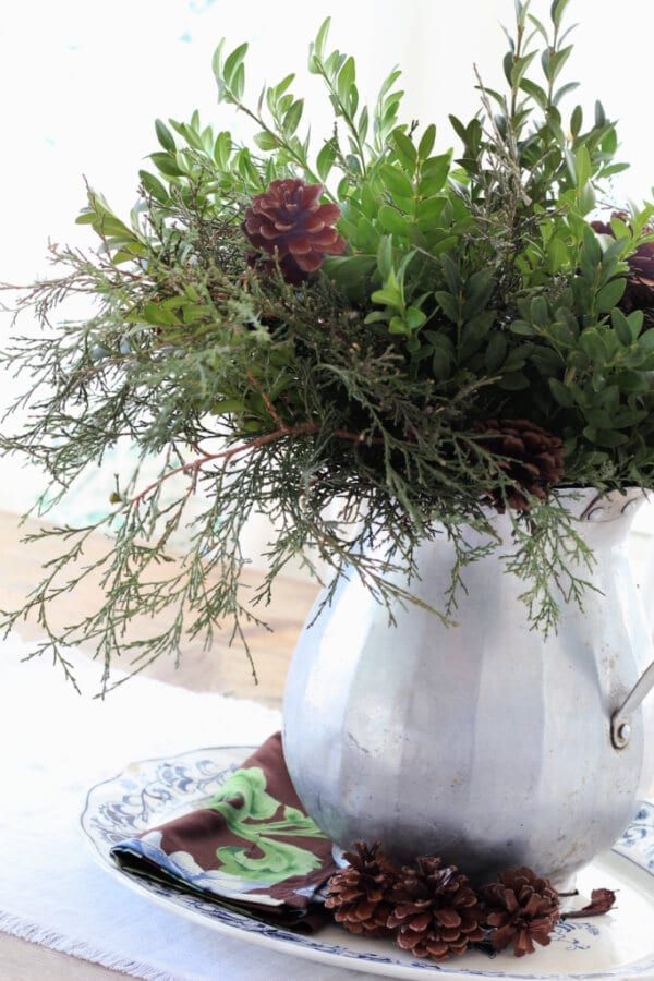 A simple winter centerpieces with foraged greenery and pine cones.