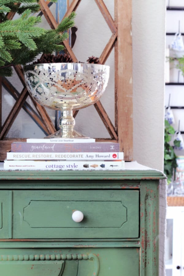 A winter vignette with books, pine cones and mercury glass.