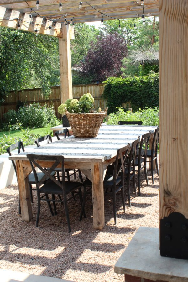 A view of our outdoor wooden dining table and black metal x back chairs.