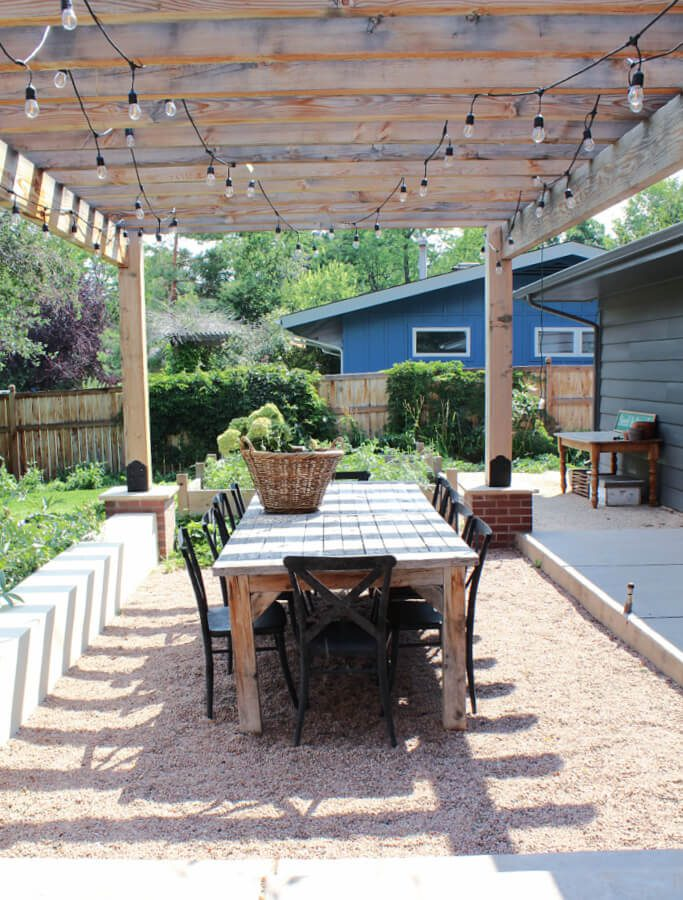 under the lights and the pergola, an outdoor dining table and chairs.