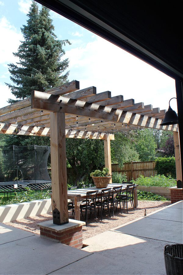 Outdoor dining perfection with pergola, cafe lights and wooden table.