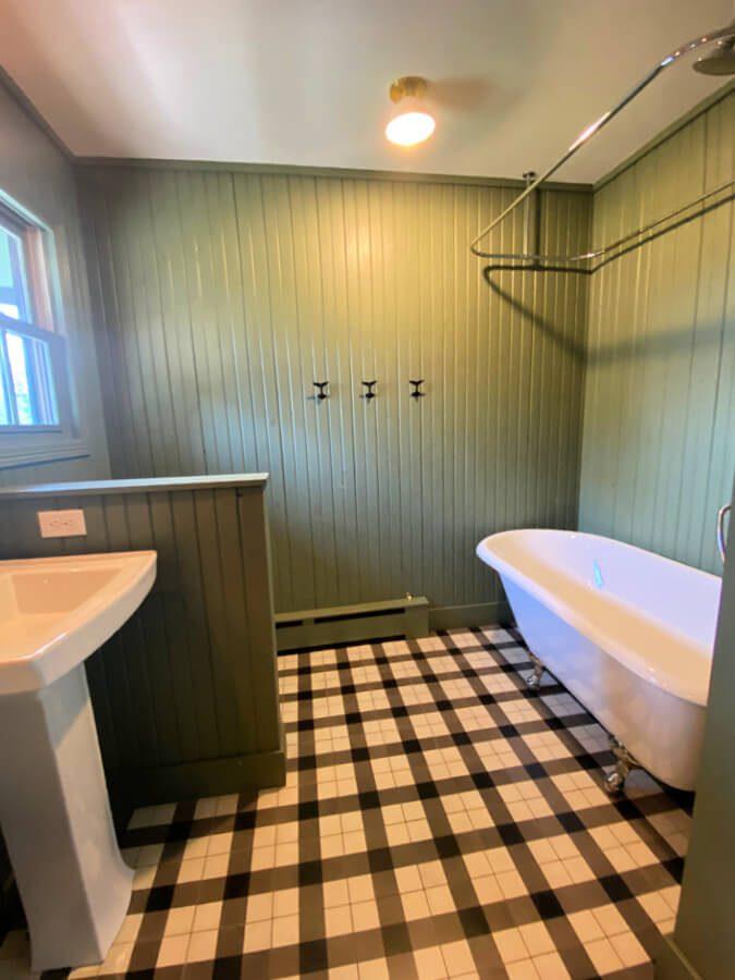 Kid bathroom with green bead board walls and vintage claw foot tub.