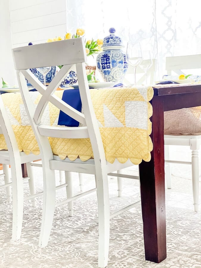Un unexpected yellow and white quilts serves as the perfct tablecloth for this Mother's Day table.
