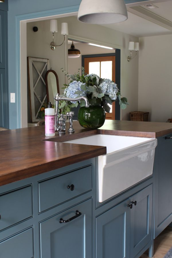 Butcher block counter tops, farm sink and gorgeous blue cabinets.