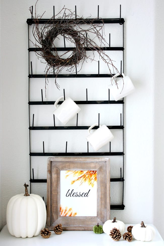 Free blessed fall printable displayed perfectly with pumpkins in front of the mug rack. Simple and easy fall decor.