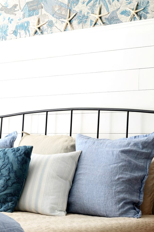 Starfish, wallpaper and calming blues make this coastal cottage master bedroom cozy and casual.