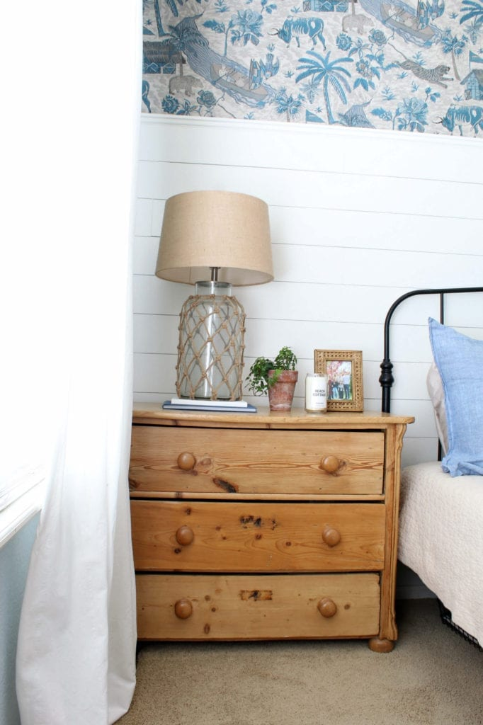 A vintage dresser with a coastal vignette makes this room feel collected and cozy.