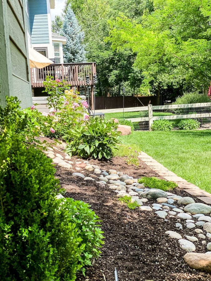 A river rock beds a beautiful touch to this backyard garden. AN easy DIY for anyone looking to ramp up their outdoor space.