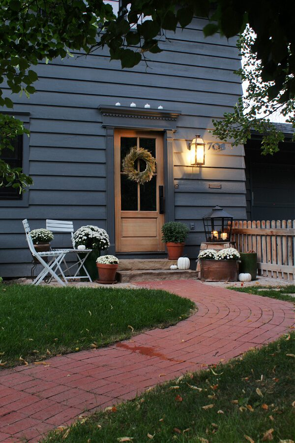A brick path leads you to our wood door and front steps decorated for Fall.