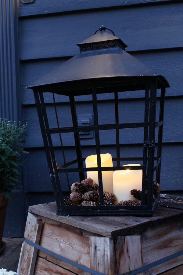 Large black lantern full of pincones and battery operated candles exudes Fall charm!