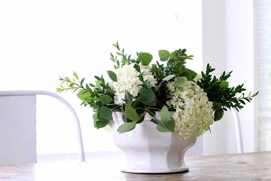 How to make a low hydrangea centerpiece with pops of fresh greenery.