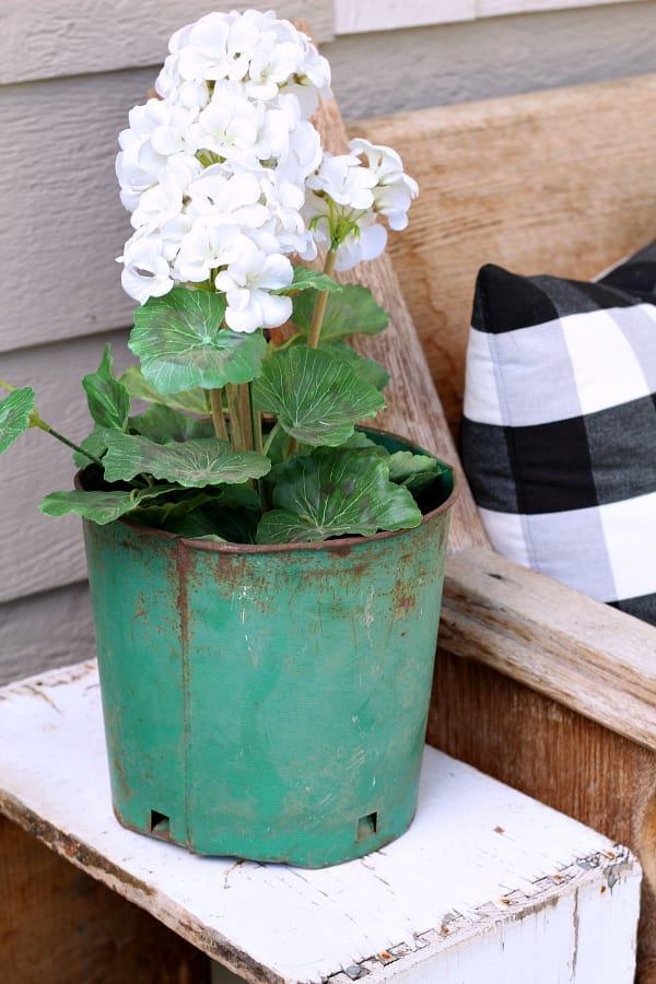 An old green garden pot hold a faux geranium and is an easy porch accessory.