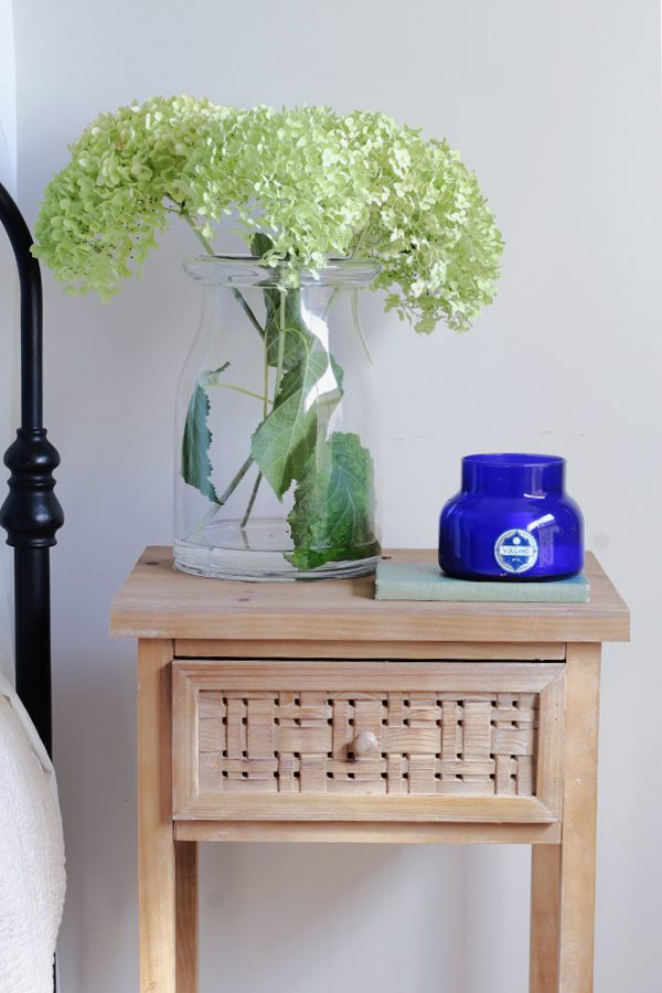 Dried hydrangeas, a volcano candle and wood nightstand.