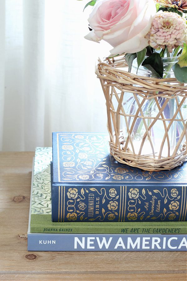 A stack of books and fresh flowers bring life to our master bedroom.