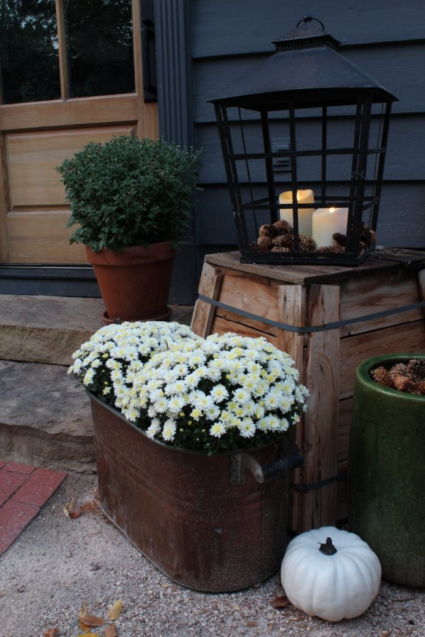 Fall on the steps of our house include mums, copper pots, pinecones, lanterns and candles.