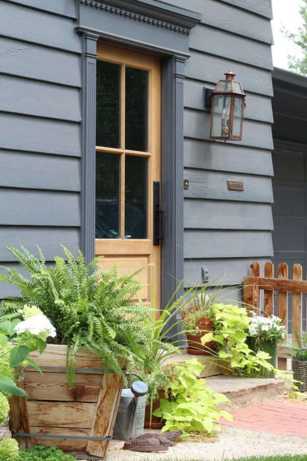 A wood front door with wondows and charm accents our peppercorn painted home.