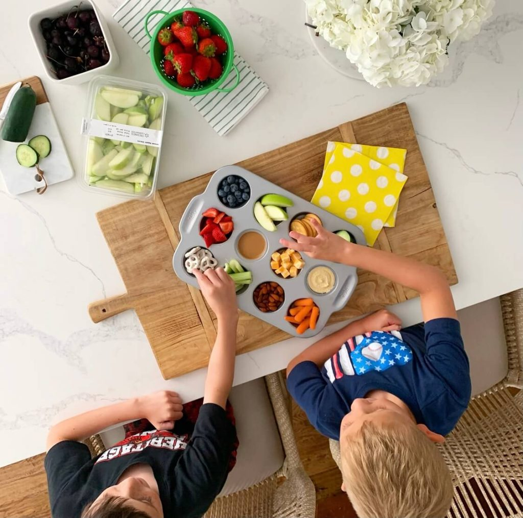 Welcome Home Saturday: Our favorite dummer lunch! | Welcome Home Saturday by popular Alabama lifestyle blog, She Gave It A Go: image of two young boys eating snacks out of a metal muffin tin.