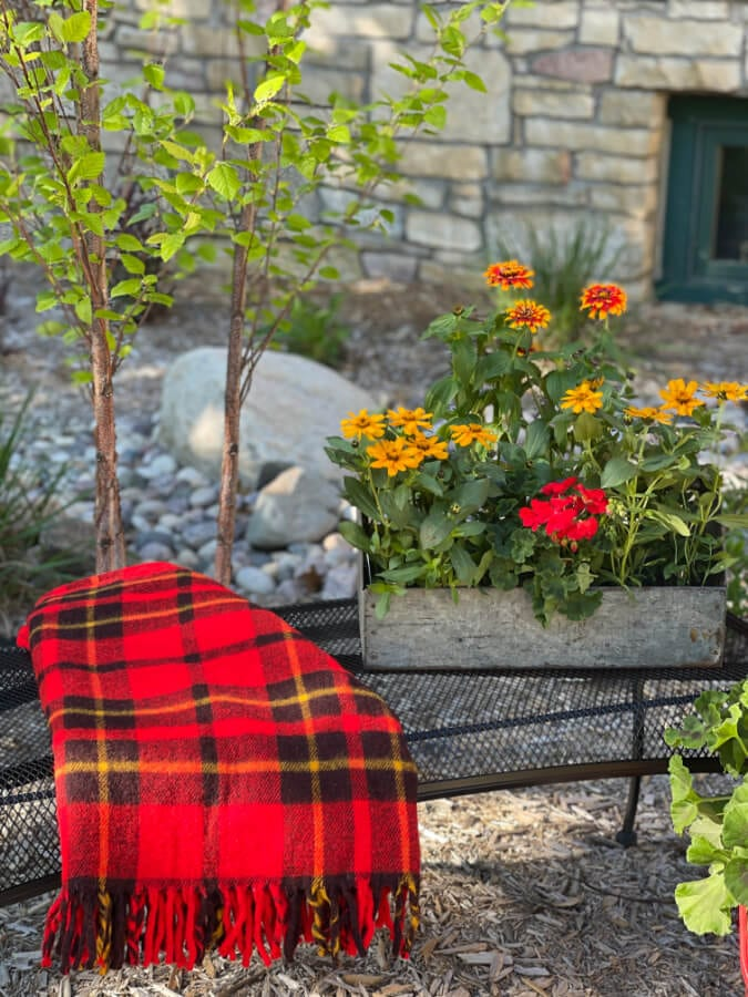 Welcome Home Saturday: Make an Old Garden Bench New With Spray Paint | Welcome Home Saturday by popular Alabama lifestyle blog, She Gave It A Go: image of an old wire bench with a metal planter box filled with flowers and a red, yellow, and black throw blanket resting on top.