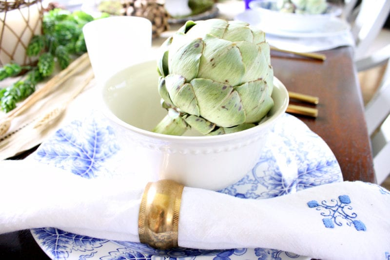 An artichoke brings an element of green to this neutral Autumn table.