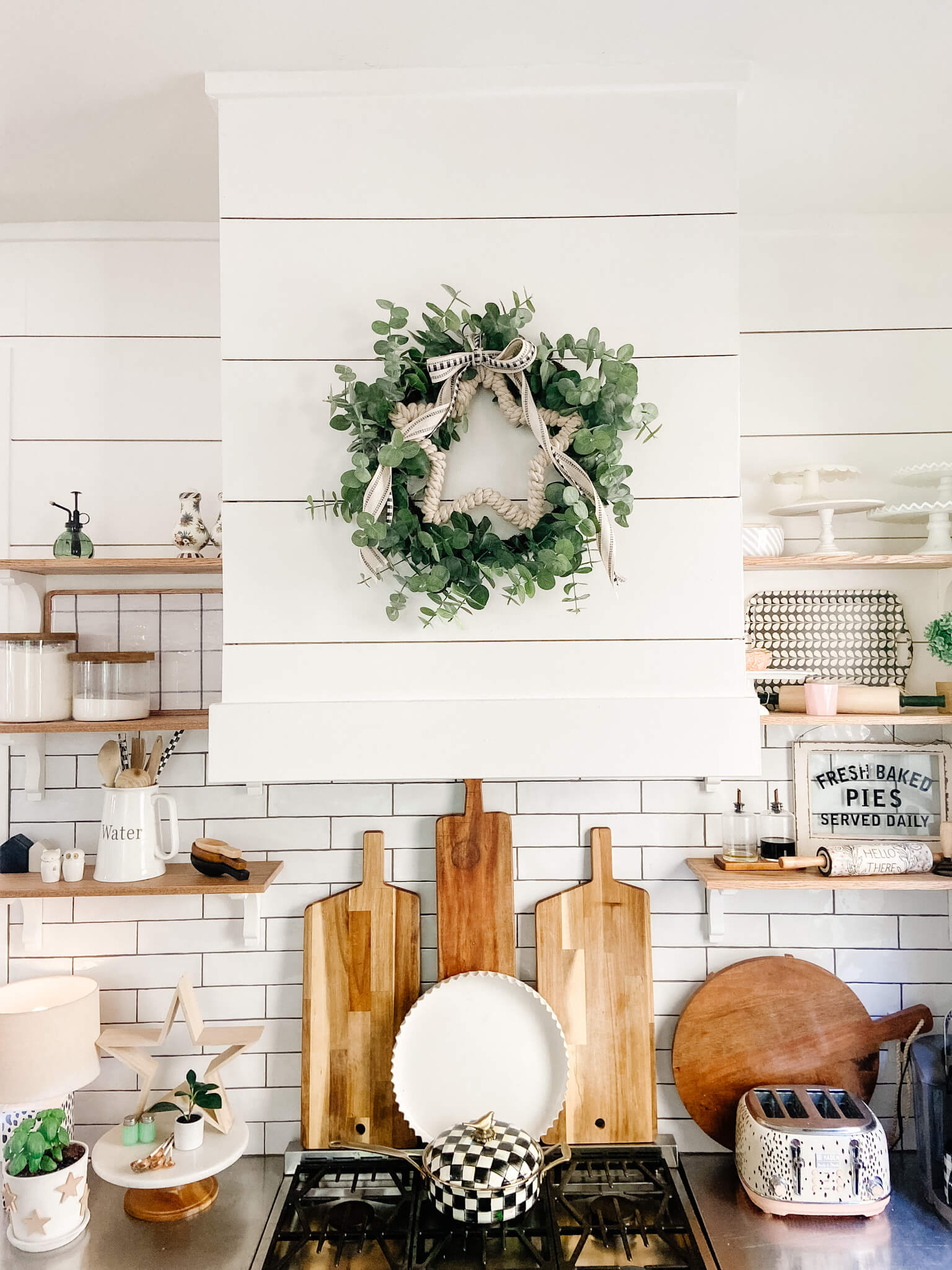 Welcome Home Saturday: Neutral Patriotic Dollar Store Wreath | Welcome Home Saturday by popular Alabama lifestyle blog, She Gave It A Go: image of a farmhouse kitchen with white shiplap walls, white subway tile backdrop, wooden cutting boards, light wood floating shelves decorated with white ceramic dishes, wooden cooking utensils, wire baskets, and filling pins, a gas range stove, and a faux eucalyptus and white pom pom wreath.