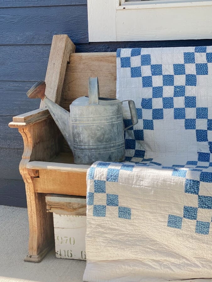 A blue and white vintage quilt on our summer porch
