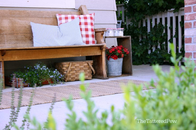 An old pew and touches of red, white & blue make this porch Summer ready!
