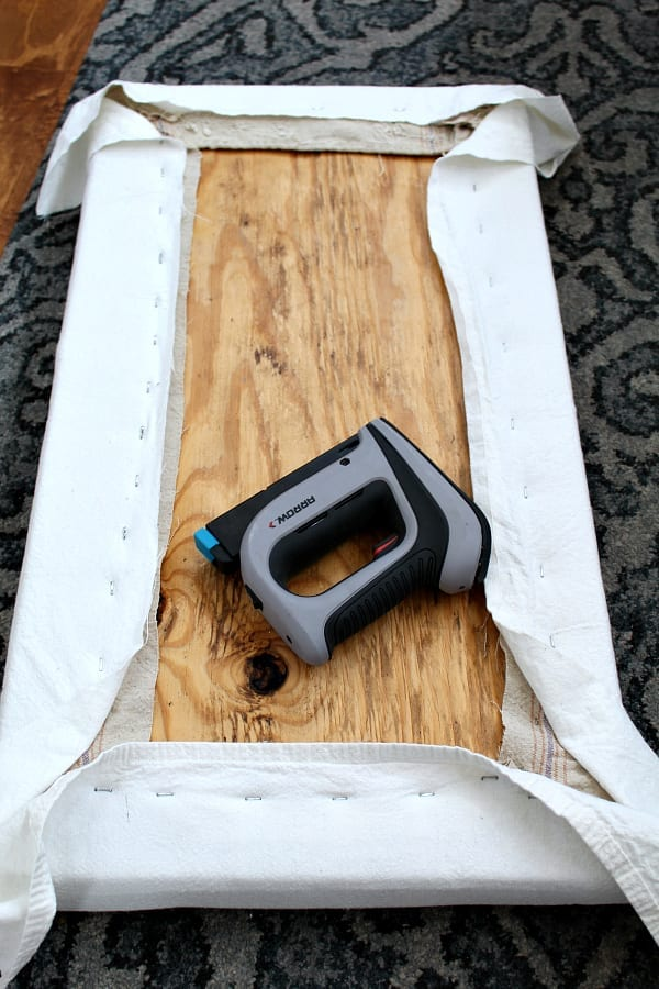 Uese a staple gun to recover a bench seat with drop cloth.