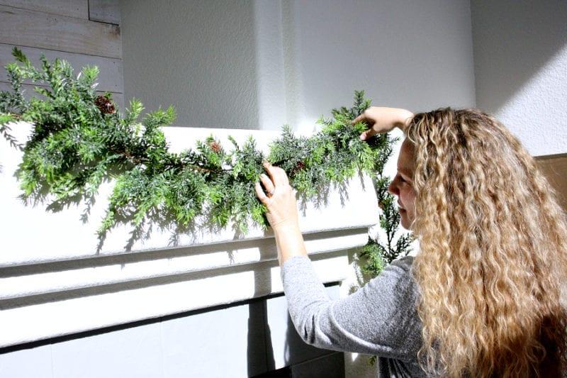 Adding garland to my Christmas mantel.