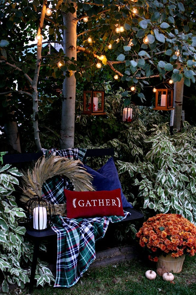 An outdoor nook with cozy lights and Fall decor.