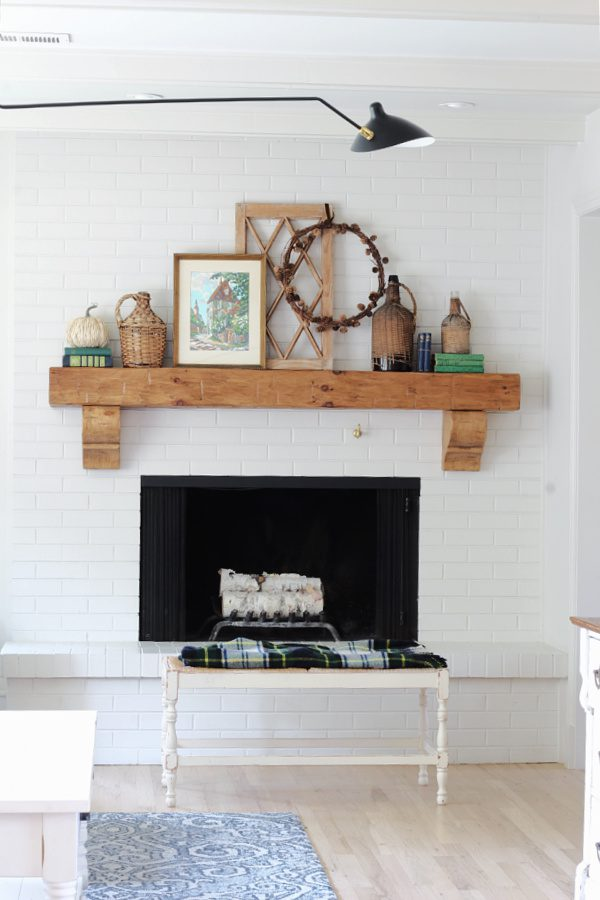 Fall mantel  with rattan, paint by number art, plaid and touches of blue and green.