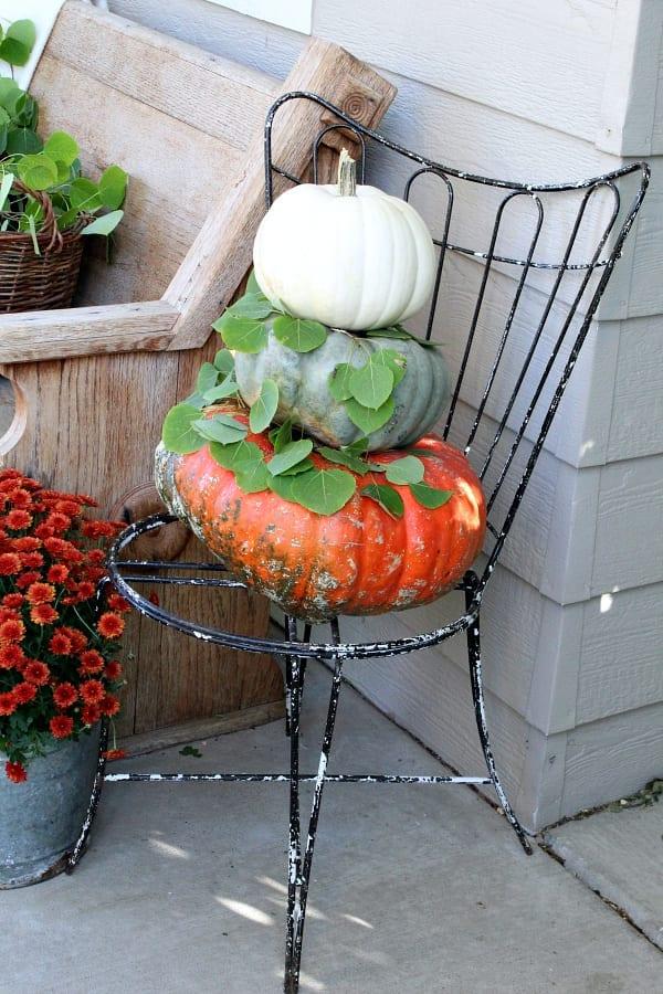 Stacked pumpkins on n old vintage chair.