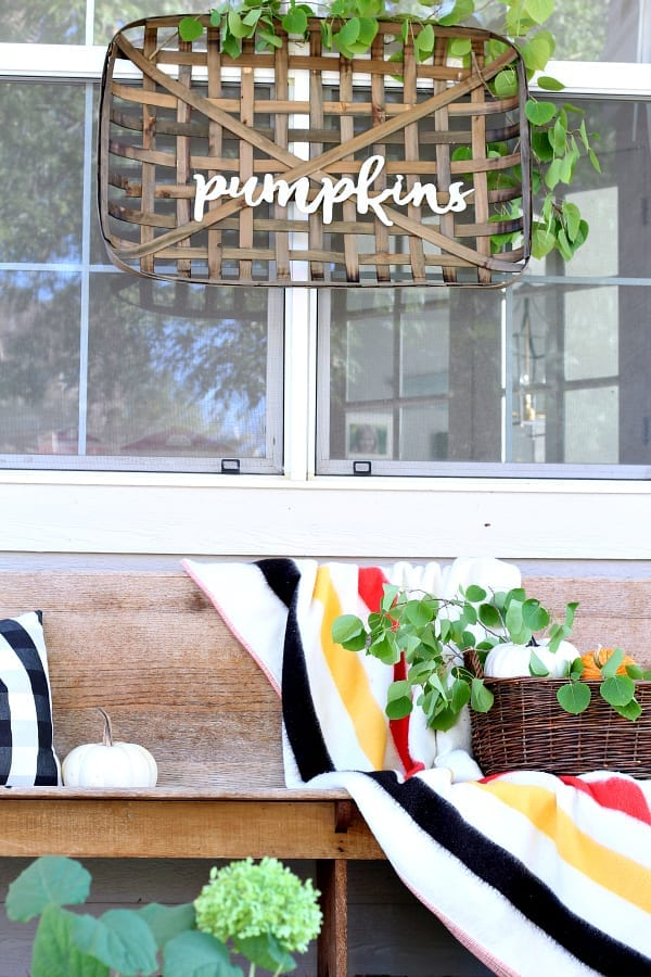 Pumpkins, basket and blankets are great ways to add vintage decor to your Fall porch.