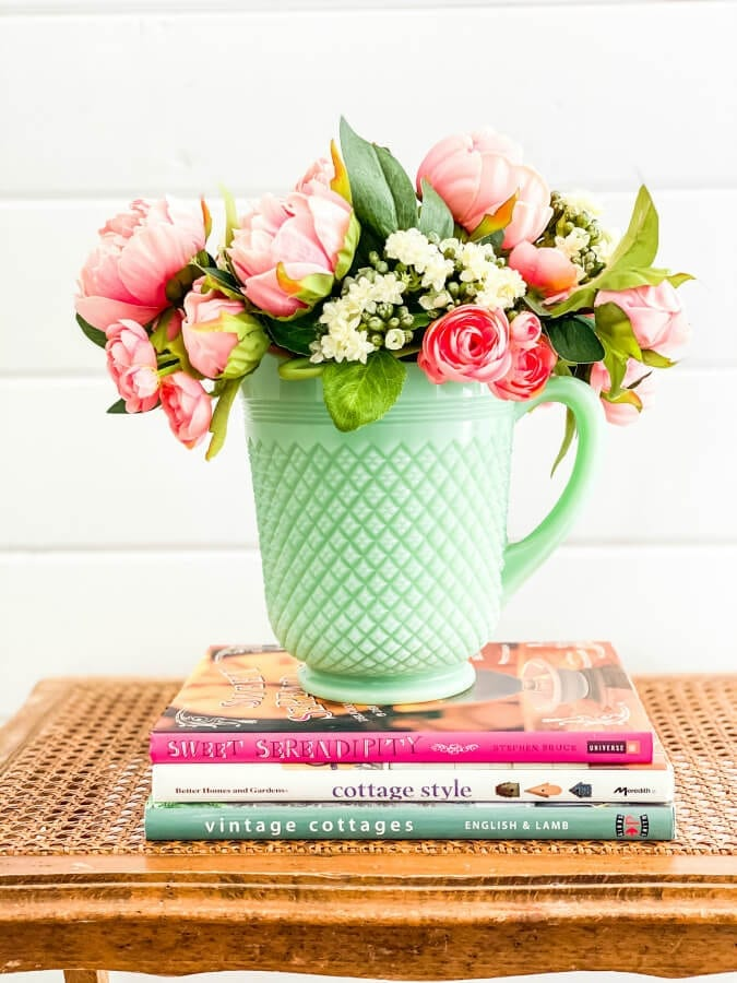 A bunch aof pretty faux flowers look perfect in this jadeite pitcher.
