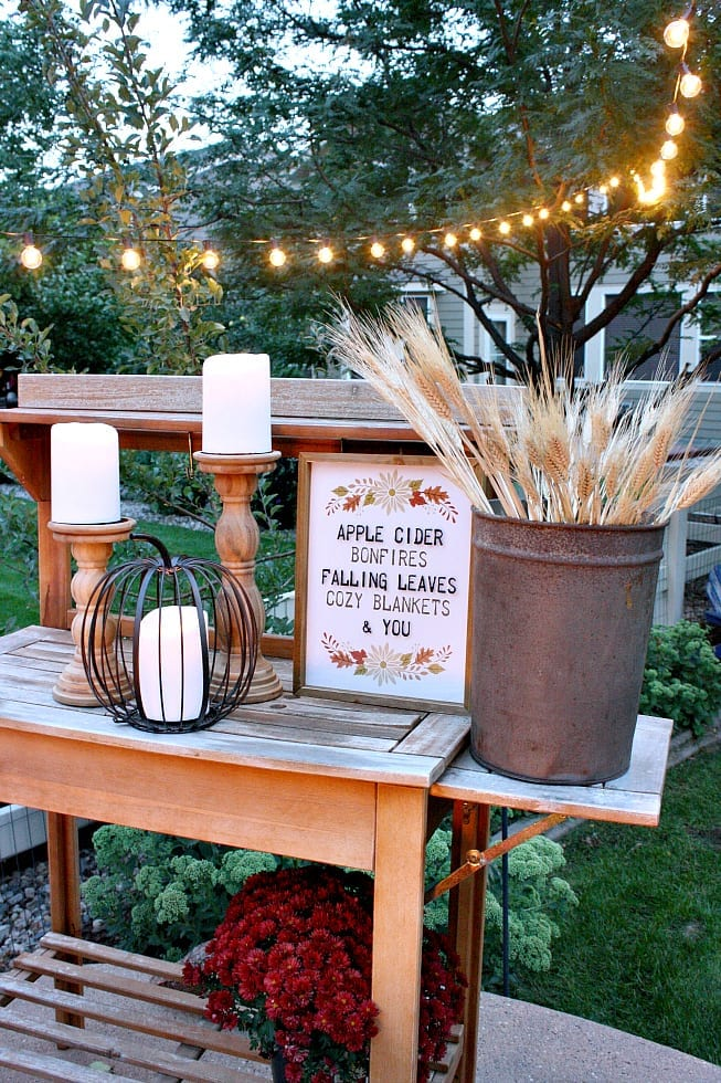 Apple cider print, metal pumpkin and wheat stems are perfect for Fall decor even outdoors.